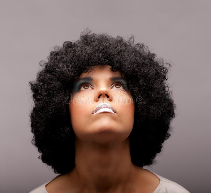Looking for the light. Portrait of a woman with an afro hair-dress, smooth skin tones, white lipstick and blue/aquamarine eye shadows looking straight up stock image