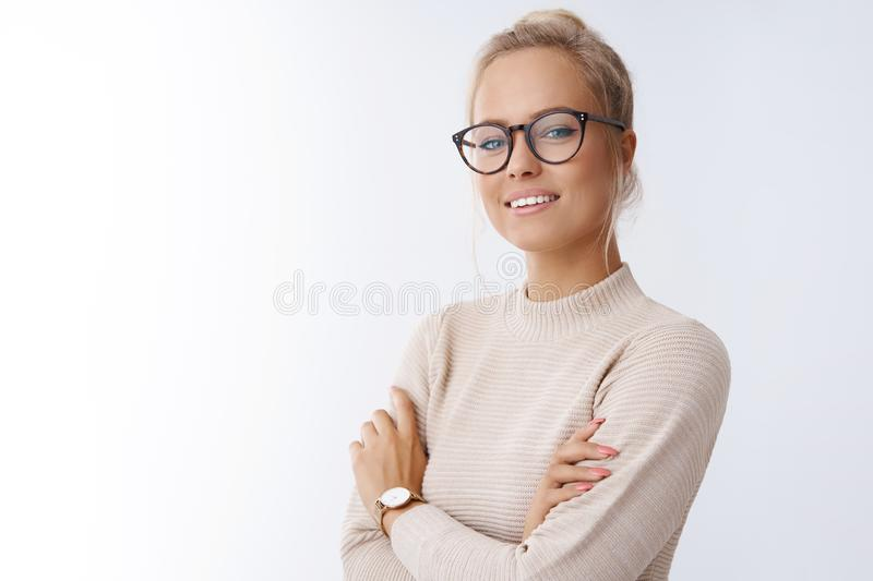 Looking like professional. Attractive successful and confident female entrepreneur with blond hair in glasses knowing royalty free stock images