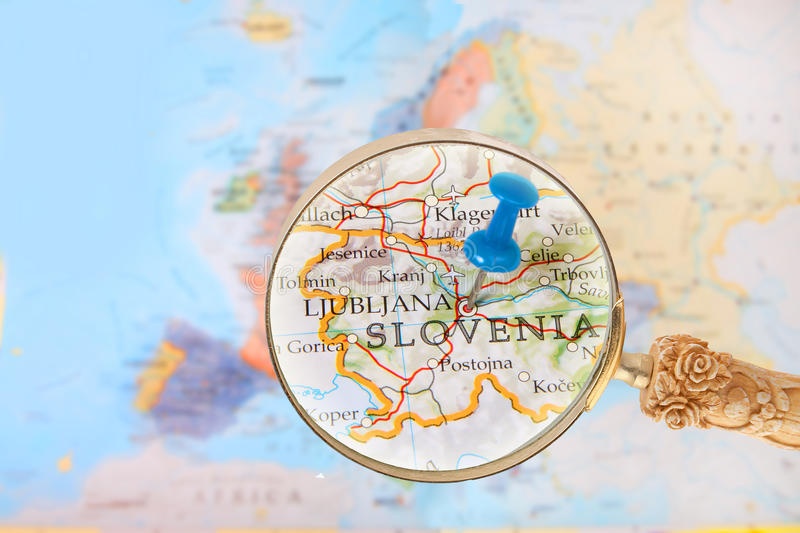 Looking in on Ljubljana, Slovenia. Blue tack on map of Europe with magnifying glass looking in on Ljubljana, Slovenia stock image