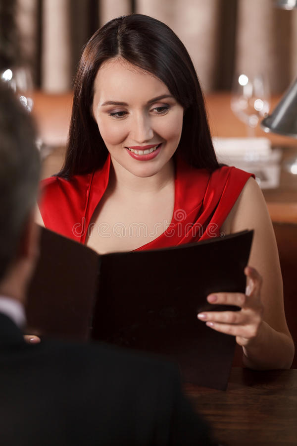 Looking at Menu. Beautiful middle-aged women reading Menu while royalty free stock photography