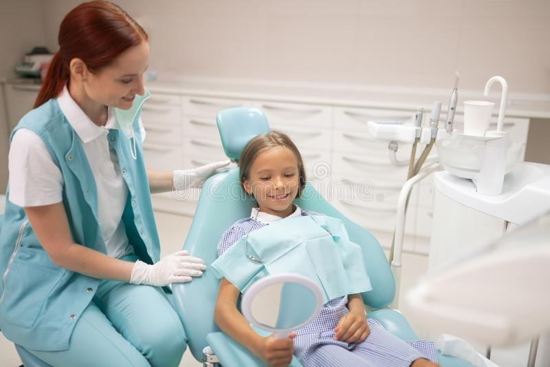 Cheerful girl looking into mirror after dental examination. Looking into mirror. Cheerful girl looking into mirror after dental examination by pleasant doctor royalty free stock image