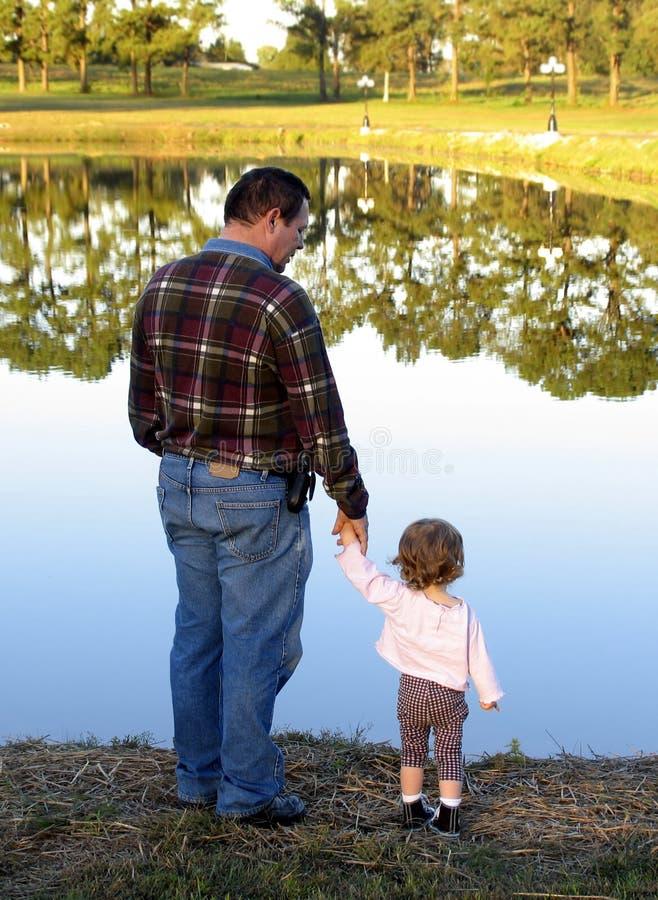 Looking at mirror lake. Father and daughter looking at beautiful reflective lake royalty free stock images