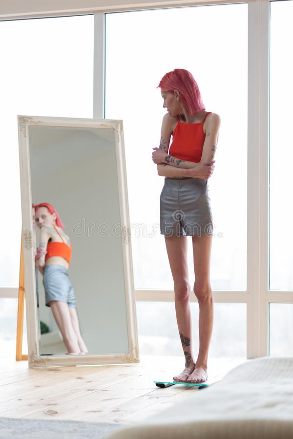 Skinny unhealthy woman wearing shorts and top looking into mirror stock image