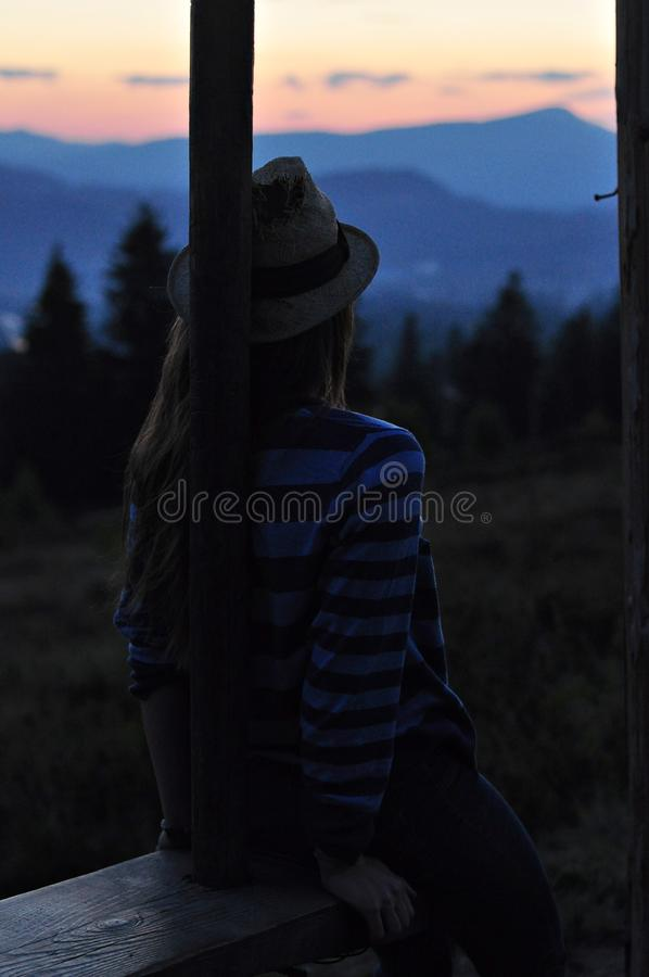 Looking at the mountains girl swinging on the swing stock image