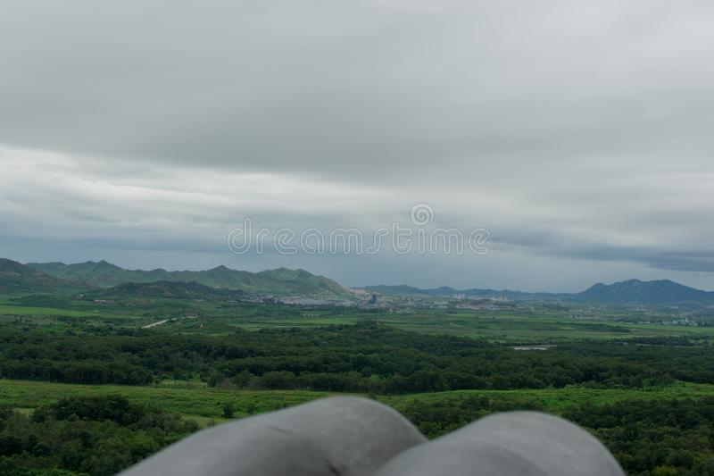 North Korean propaganda village. Looking into North Korea, featuring binoculars stock image