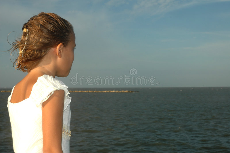 Looking off at sea. Little girl in a white dress stands facing the ocean off a stone wall. The wind blow threw her hair. Big smile on her face royalty free stock photo