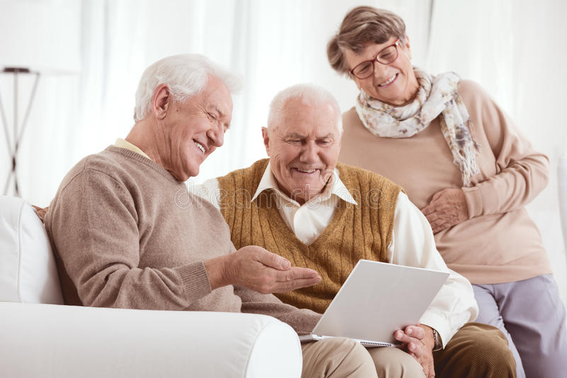 Looking at old photos. Two older men and a women looking at old photos on a laptop stock image