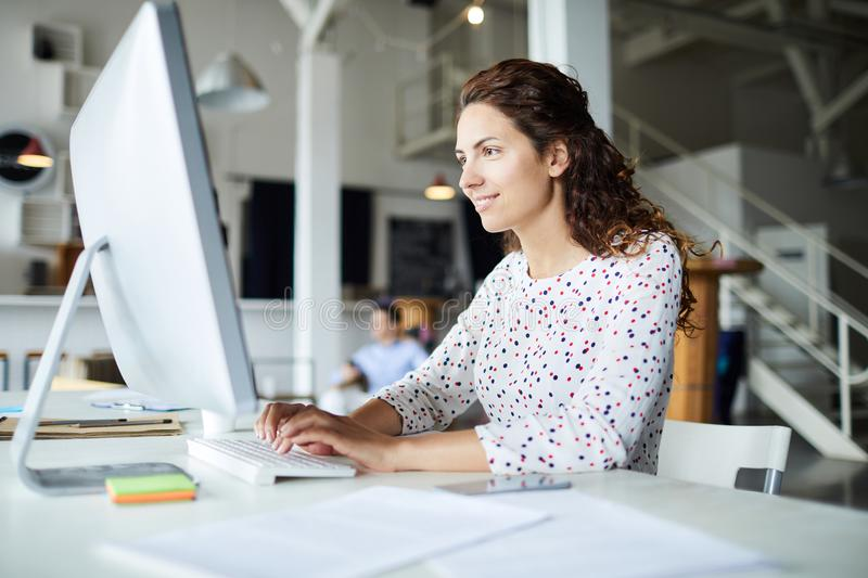 Looking through online data. Young smiling businesswoman siting by desk in front of computer monitor, typing and reading online data royalty free stock image