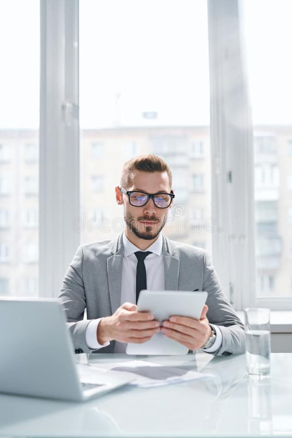 Looking through online statistics. Young serious economist in formalwear concentrating on reading online data in tablet while working in office stock photography