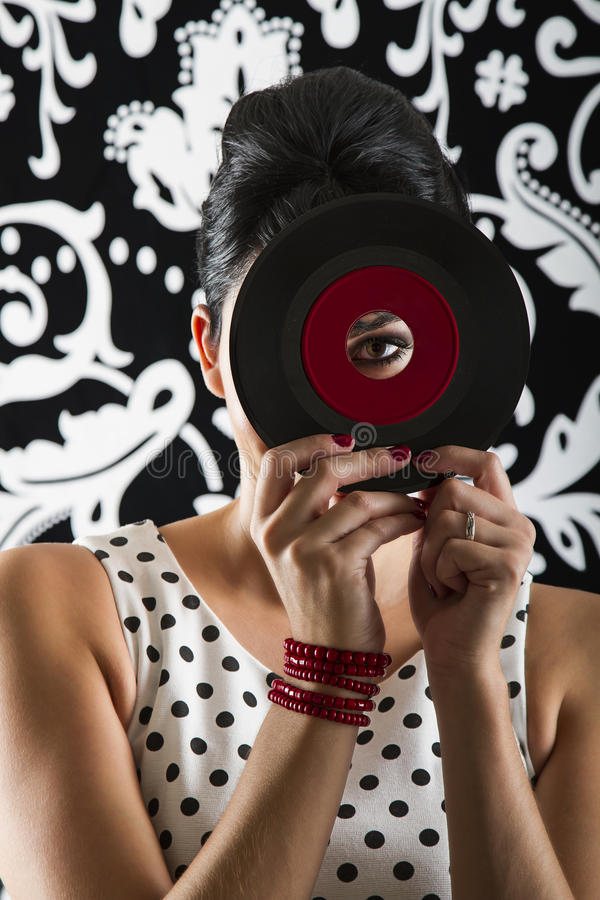 Looking from the other side. Young woman looking through the hole of a small dusty record with a red label royalty free stock photography