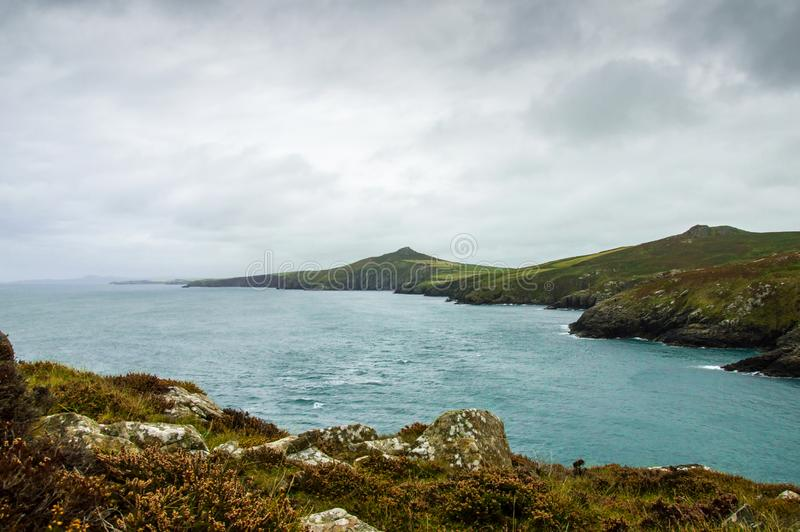 Looking out across the sea, cliffs and hills along the wild Pembrokeshire coast. With dark clouds on a September day. Wales. stock photos