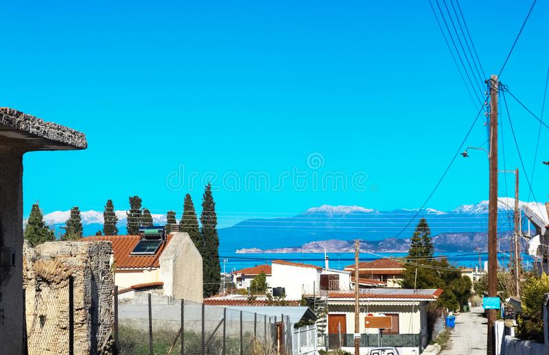 Looking across water to snow covered mountains from steep road in village of Corinth Greece royalty free stock images