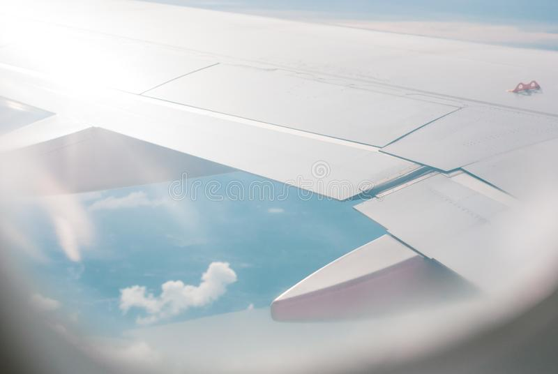 Looking out through airplane window view photo showing its wing and blue sky, travelling photo royalty free stock photography