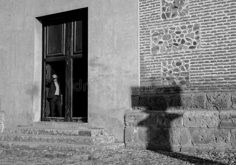 Looking out at Alhambra - Granada, Spain. A black and white image of a man looking through a doorway at Alahambra - Granada - Spain stock image