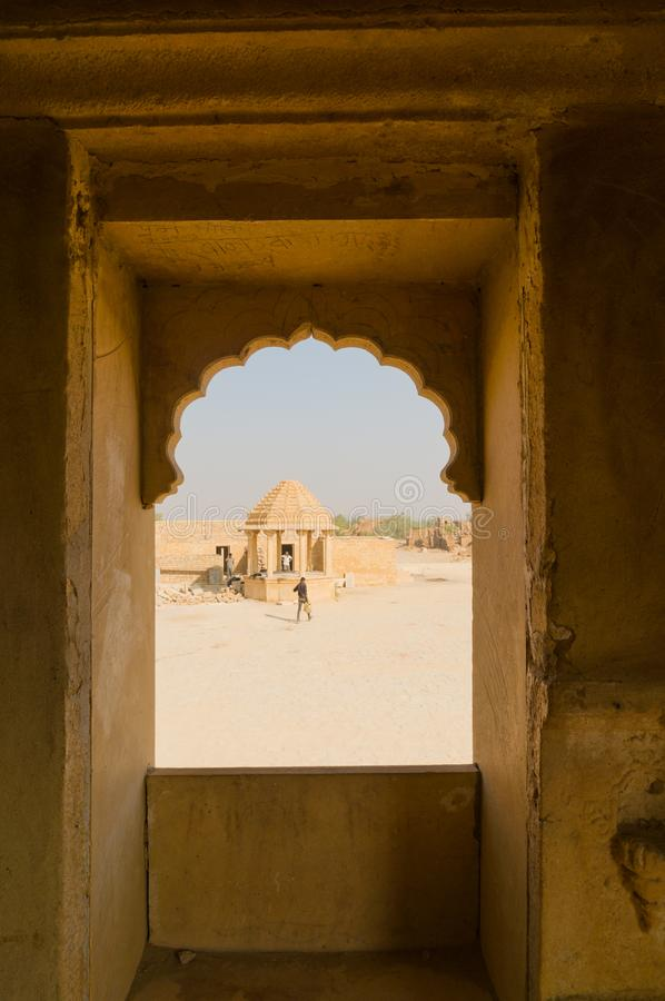 Looking out an arched stone window of rajasthani design onto the haunted ruins of Kumbalgarh Jaisalmer. Rajasthan, India. This popular tourist destination is royalty free stock images