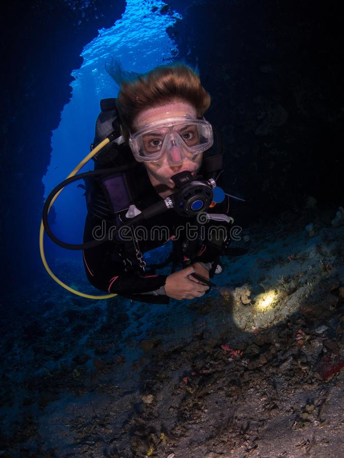 Cave diving in Alor. Looking out from the inside of an undersea cave as a diver swims directly towards the photographer holding a torch, cave entrance royalty free stock photography