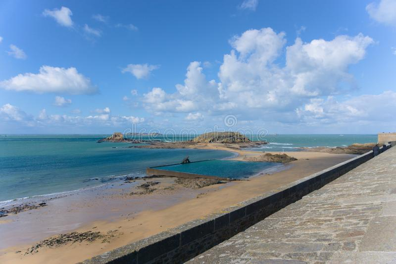 Looking out over the ocean in Saint-Malo France onto the rock fortress and tide pools. Looking out on the ocean from the Saint-Malo boardwalk, ocean tide pool stock image