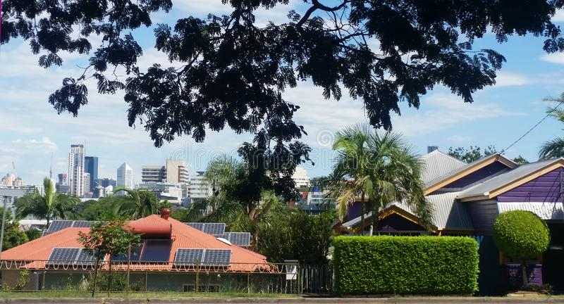 Looking out over the rooftops of Brisbane suburban house with solar panels to the downtown skyline in the distance framed by the l stock images