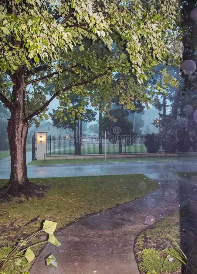 Looking out at street and fence and trees in urban neighborhood during a heavy rainstorm on stormy dark day with drops visible and royalty free stock photo