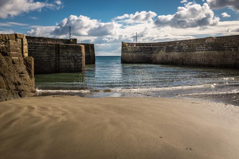 Looking at out towards the entrance of Charlestown harbour in Cornwall, England, shot from the sands. Against a bright blue sky stock image