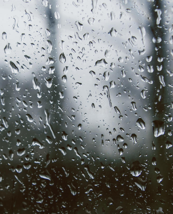 Looking out of a window covered with rain drops. Looking out of a car window covered with raindrops. A grey, dull, rainy day in winter or late autumn stock photo