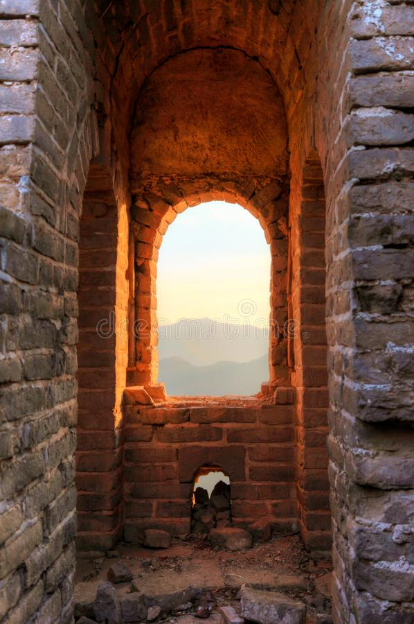 Looking out the window of guard tower during a sunset on the unrestored great wall of China royalty free stock photo