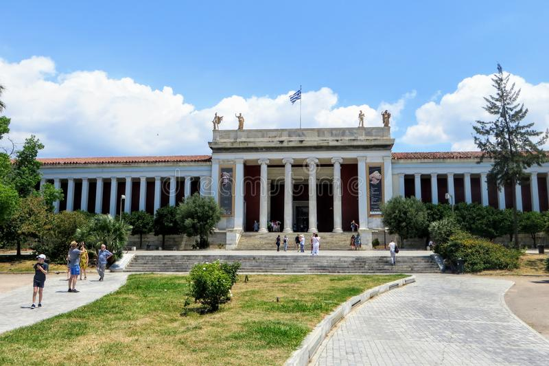 Looking outside at the front of the world famous National Archaeological Museum in Athens, Greece.  Several visitors are walking t. Athens, Greece - July 13th stock photography