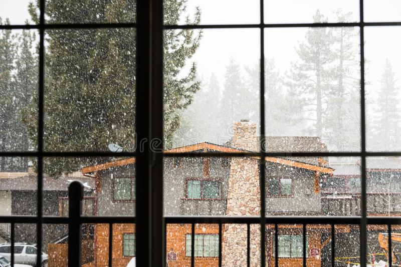 Looking outside through a window at falling snow, South Lake Tahoe, California stock image