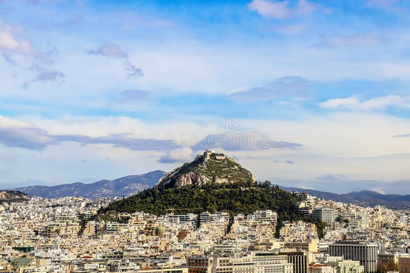 Looking over the rooftops to Lycabettus Hill - the highest spot in Athens Greece with church of St George and a resturant where to. Urists can enjoy the view royalty free stock photo