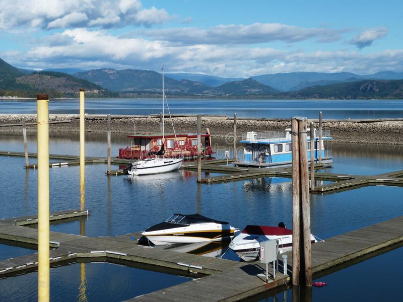 Overlook of Salmon Arm Boats in Harbour. Looking over Salmon Arm Harbour in British Columbia, where a few boats are docked. Blue sky, blue river, blue mountains royalty free stock photo