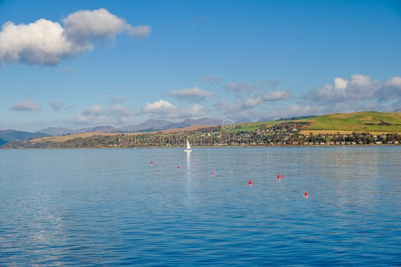 Looking over to Dunoon from the front at Gourock and a single Ya. Looking over to Dunoon from the front at Gourock on a bright Octobers day with a single white royalty free stock photo