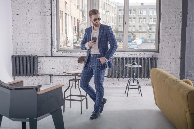 Looking perfect. Full length of handsome young bearded man in full suit and sunglasses looking away while standing at home. Using stock images