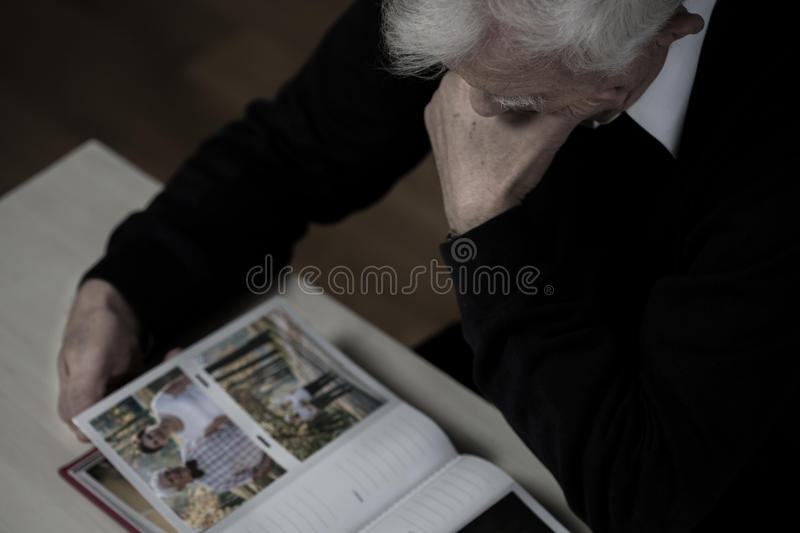 Looking at photos with wife. Man in mourning looking at photos with wife stock photography