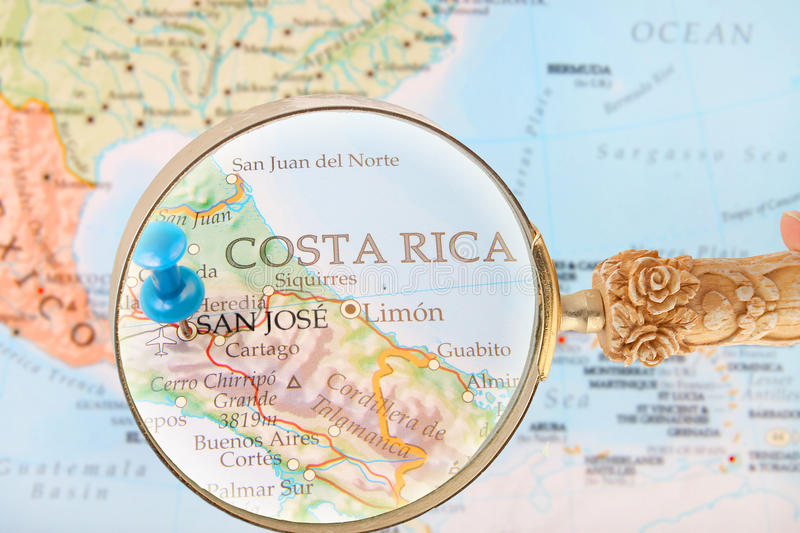Looking in on San Jose, Costa Rica. Blue tack on map of Central America with magnifying glass looking in on San Jose, Costa Rica royalty free stock photo