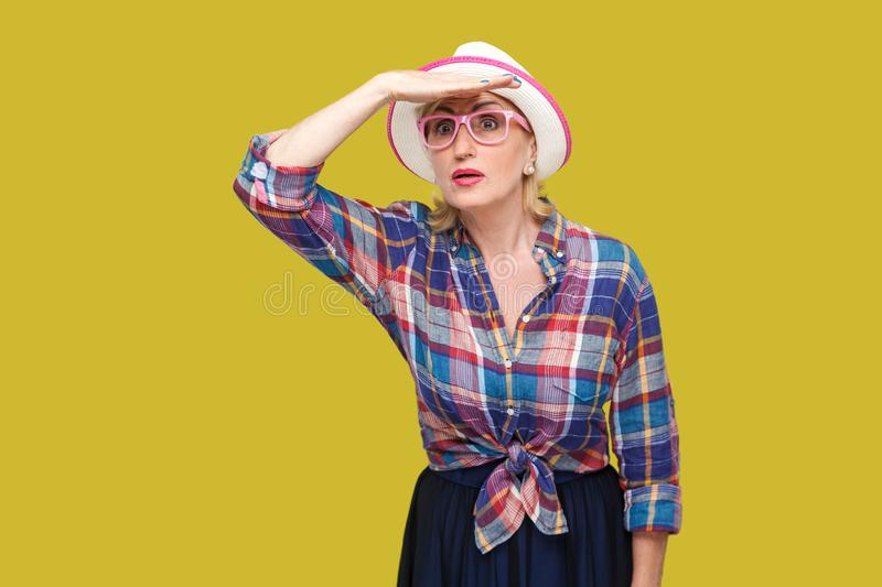 Looking for something so far. Portrait of attentive modern stylish mature woman in casual style with hat and eyeglasses standing. With hand on forehead. indoor royalty free stock image