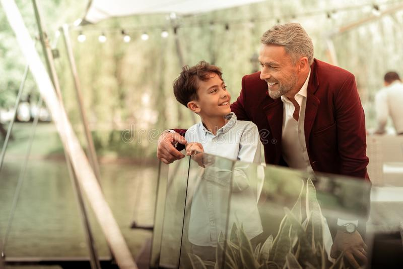 Bearded grey-haired father looking at his lovely handsome son stock photos
