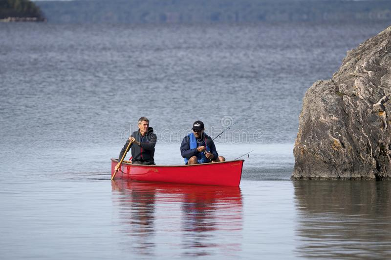 Looking for the spot to catch a fish on Georgian Bay, Ontario. Two active fishermen on Georgian Bay near Christian Island are hoping to find the spot to catch stock photos