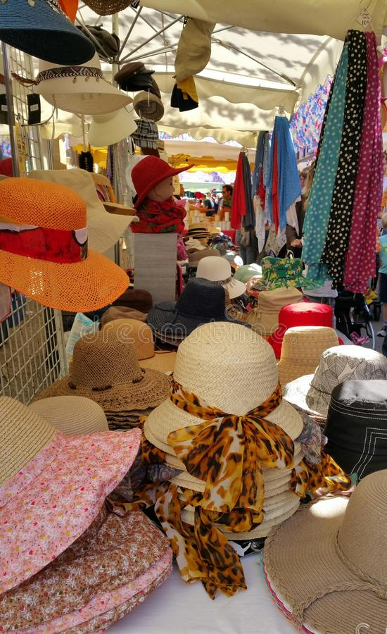 Assorted ladies colourful summer hats and scarves. Looking at street market stall displaying colourful array of ladies sun hats in cotton and straw and selection royalty free stock photos