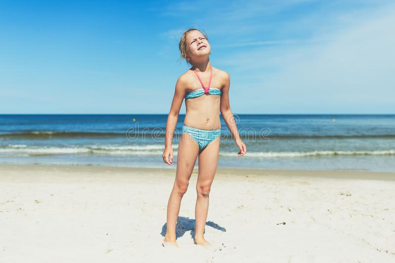 Looking into the sun - a little girl on a sandy beach staring straight into the sun royalty free stock photo