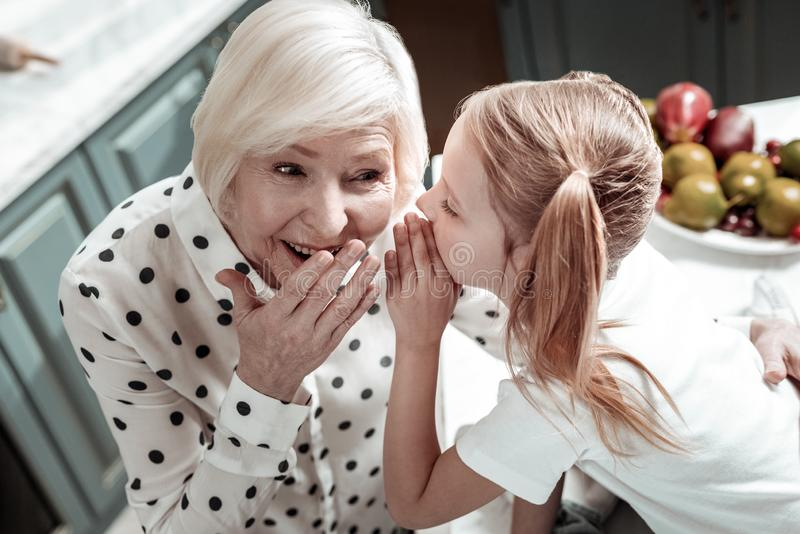 Emotional granny touching her mouth while little girl sharing secrets with her royalty free stock photos