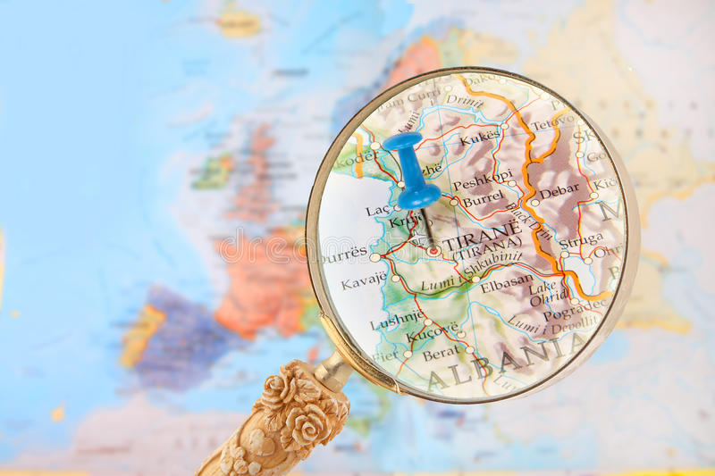 Looking in on Tirane, Albania. Blue tack on map of Europe with magnifying glass looking in on Tirane, Albania stock image