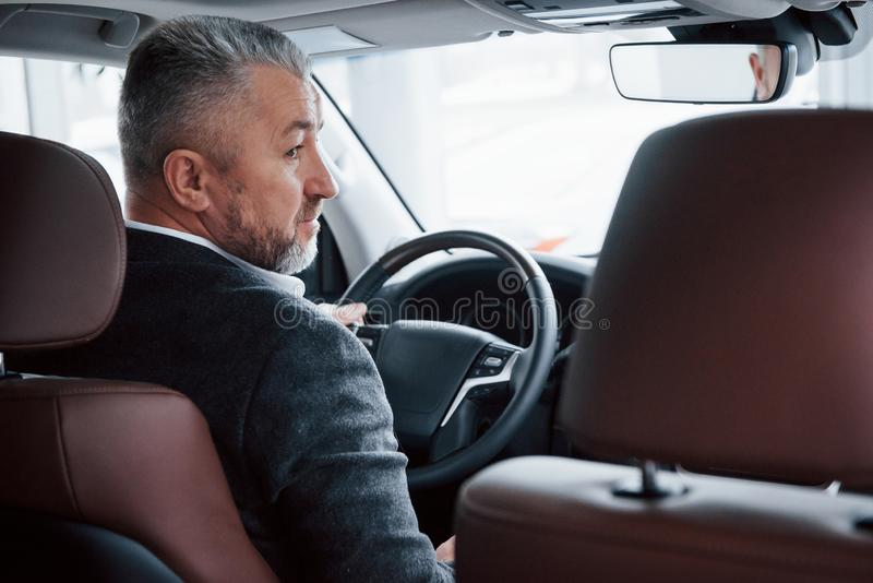 Looking to the side. View from behind of senior businessman in official clothes driving a modern new car stock photography