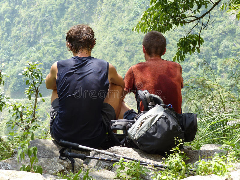 Looking to the valley. Tourists having a rest and sitting on stone - Annapurna Circuit trek stock image