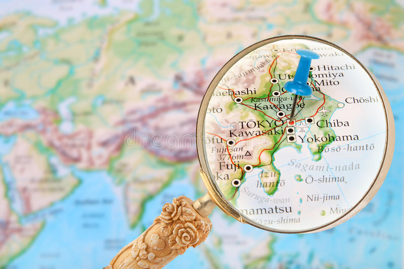 blue tack on map of the world with magnifying glass looking in on tokyo japan