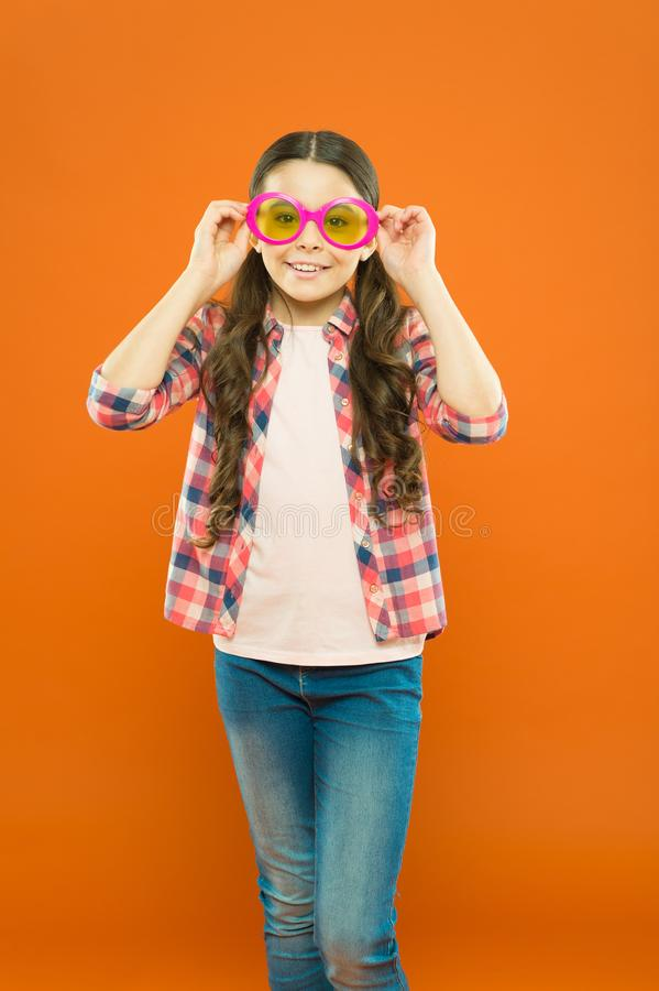 Looking trendy. Fashionable party girl on orange background. Adorable party girl wearing fancy glasses. Cute small child. Looking through party goggles with royalty free stock photo
