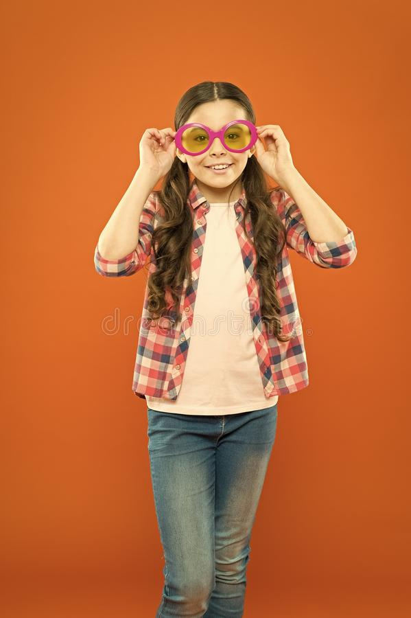 Looking trendy. Fashionable party girl on orange background. Adorable party girl wearing fancy glasses. Cute small child royalty free stock photography