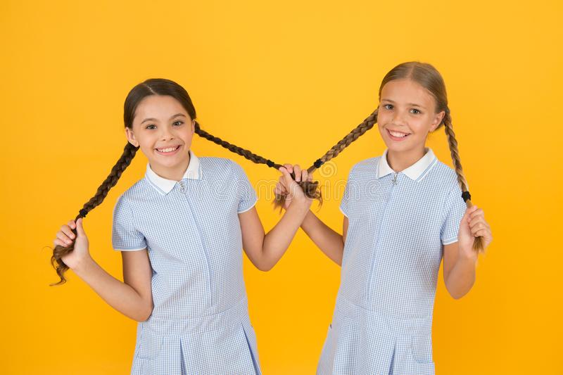 Looking trendy. sisterhood concept. best friends. vintage style. small girls in retro uniform. old school fashion. back. To school. happy beauty with pigtails royalty free stock photo