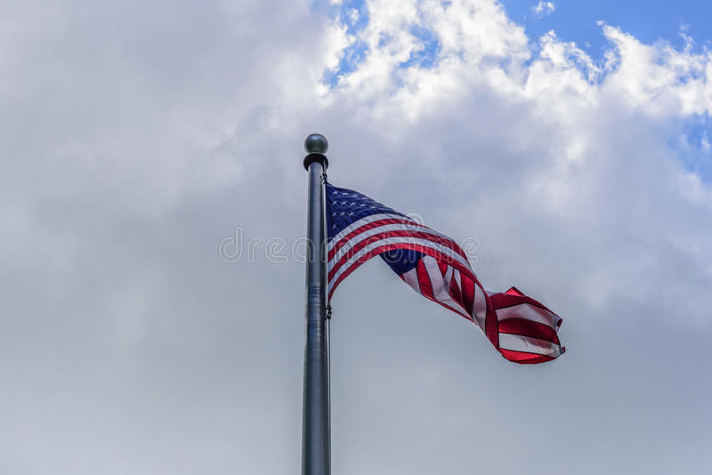 Looking up at American flag waving in clouds stock photography