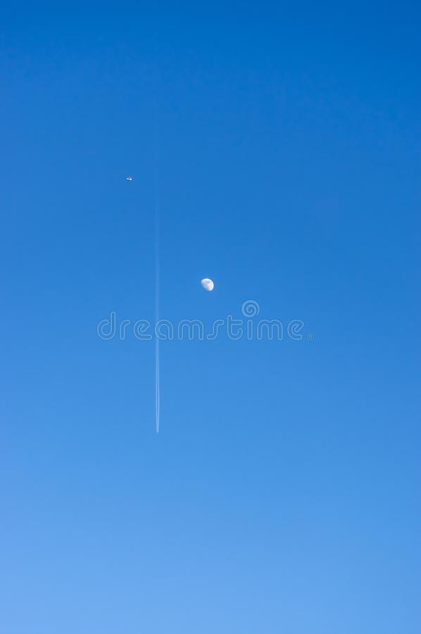 Looking up into the bright blue and cloudless sky with moon and a passenger plane with contrails and a small plane in the stock photography