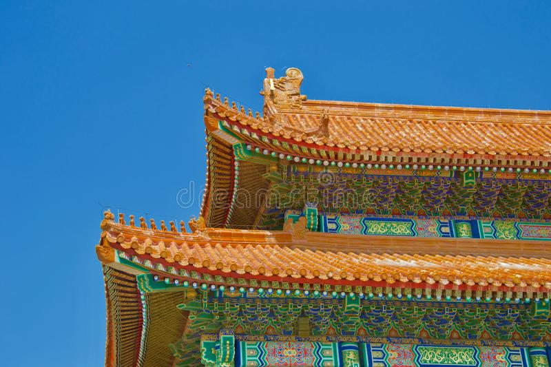 Bright roof of traditional Chinese building against blue sky - orange tiles and ornate painted walls royalty free stock photo